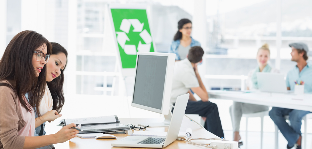 Casual group artists working at desks with recycling sign in background at a bright office
