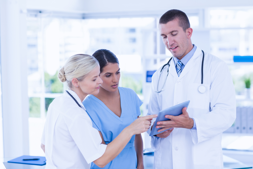 Doctors looking together at tablet in medical office-1