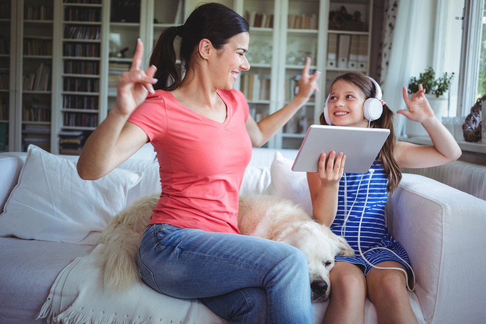 Excited mother and daughter using digital tablet and dancing at home